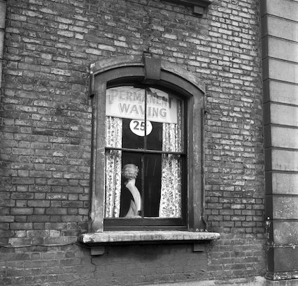 Mannequin head wearing a curly wig displayed in a sash window. c.1955