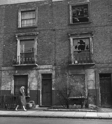 A woman walks along a residential street. c.1955