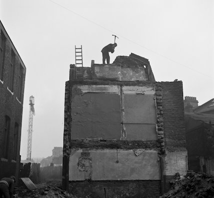 Man wielding a pickaxe on a building being demolished. c.1955