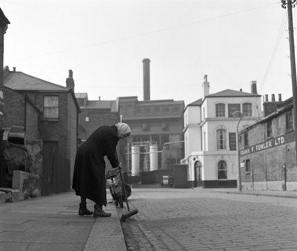 Woman sweeping kerb. c.1955