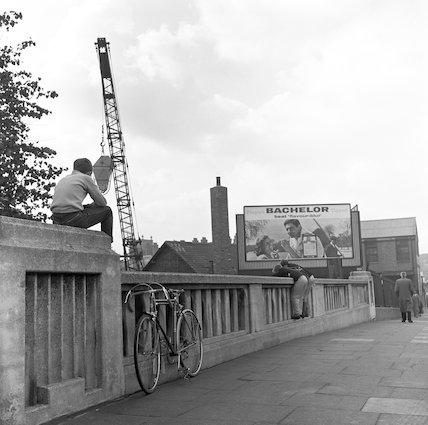 A boy sits on the parapet of a bridge. c.1955