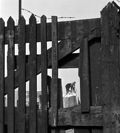 Two demotition men viewed through gate. c.1955