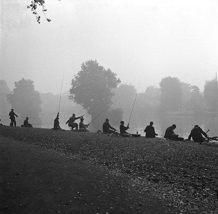 People fishing next to lake. c.1955