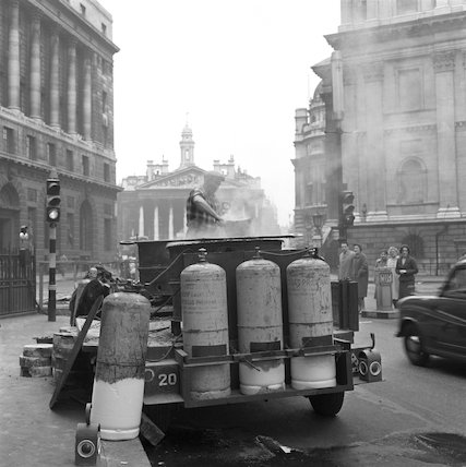 A workman mixing tar. c.1955