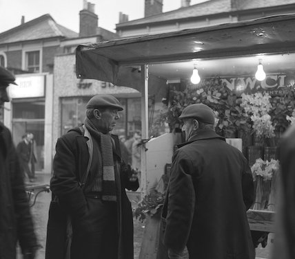 Two men in front of a flower stall. c.1955