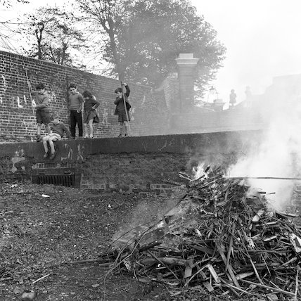 Children standing on a terrace behind bonfire. c.1955