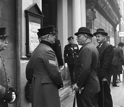Men in suits talking to Chelsea Pensioners. c.1955