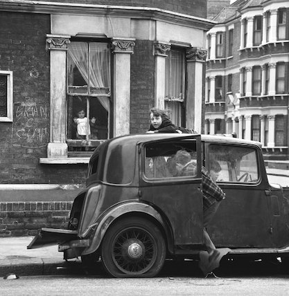 Children playing on and around a broken down car. c.1955