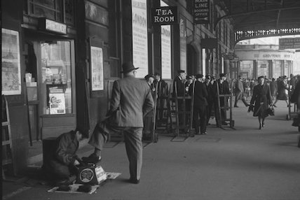 Boy shining shoes outside the Tea Room at Victoria Station, 1950