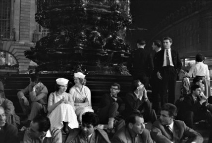 Men and women sitting in Piccadilly Circus; 1960
