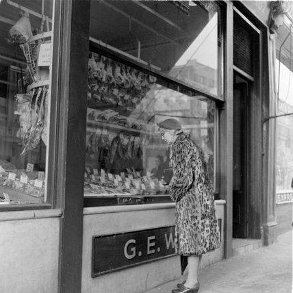 Woman looking  in a butchers shop window; 1957