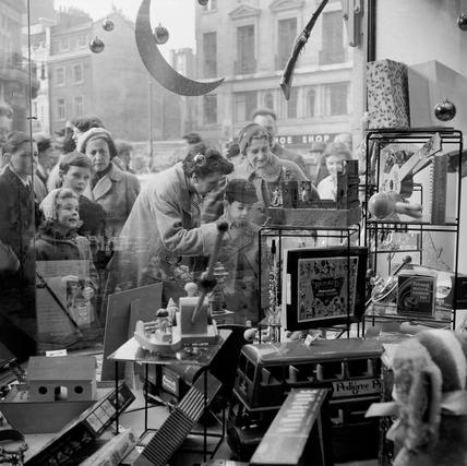 Children peer into Hamleys toy store window: 1957