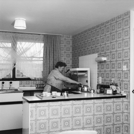 A women in the kitchen of a flat at the Marquess Estate: 1974