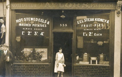 Postcard view of an eel and pie shop: 20th century