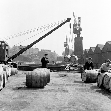 Barrels of wine are unloaded at London Docks: 1953