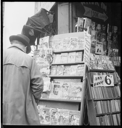 A man browses a magazine stand outside a  bookshop: 1955