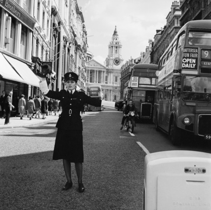A policewoman controlling traffic: 1964