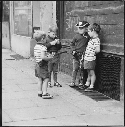 Children play in the street with toy guns: 1963