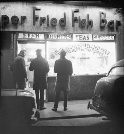 Three men stand outside The Super Fried Fish Bar in Soho: 1964