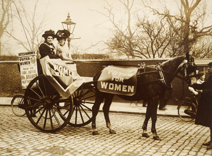 Unidentified Suffragettes riding press cart: 1909