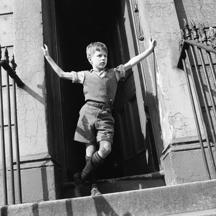 Boy standing in open doorway: 1957