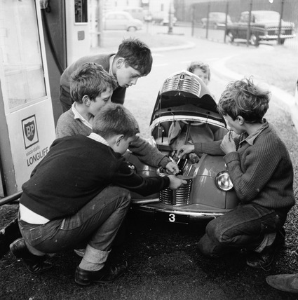 Children playing with miniature car: 1965