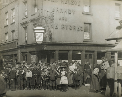 Crowd outsdie a wine and brandy store: c.1900