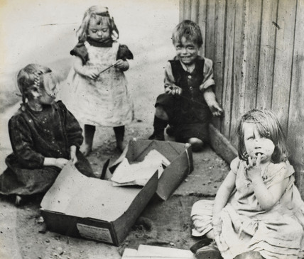 Poor children playing with their pavement toys: c.1900