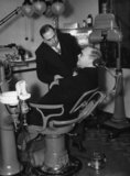 Sir (Howard) Kingsley Wood trying out a dentist's chair at a public health exhibition.