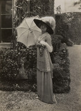Model holding a parasol wearing a polka-dot cross-over dress, by Lucile