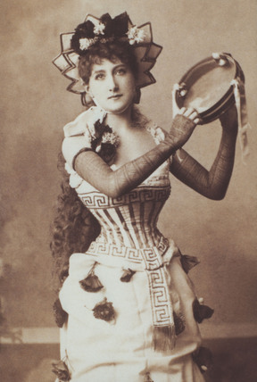 Maude Branscombe in character holding a tambourine, photo W&D Downey Photographers