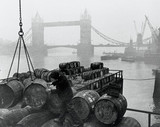 Unloading barrels at London docks, near Tower Bridge, London, c 1930s.