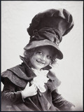 Smiling child wearing a huge velvet hat with matching velvet jacket, 1900.