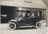 Motor car parked outside a garage, Manchester, c 1912.
