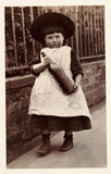 Small girl carrying a bottle, 1898.