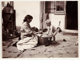 Woman washing a baby in a tin bath, c 1900.