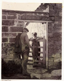 Two men talking over a gate, c 1905.