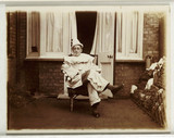 Smoking man dresed as a clown, c 1930.