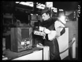 Woman inspecting an aerodyne radio, Radiolympia, Olympia, London, 1934.