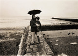 Couple sheltering under an umbrella, 1968.
