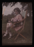 Girl sitting in a chair holding flowers, 1908.