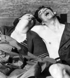 Couple sleeping in deckchairs on the beach