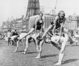 Young women playing leapfrog on the beach.