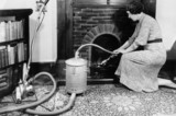 Woman vacuuming the fireplace, 7 March 1936.