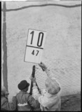 Race worker holding pit signal, 1930s.