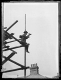 Horace Nicholls on a scaffold while taking a photograph, c.1903.