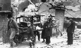 Family carrying belongings from their bombed house, London, 1940.