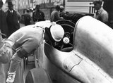Woman looking at the cockpit of a Mercedes-Benz racing car, Berlin, 1932.