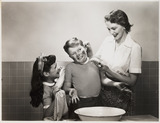 """Mother washing her son's face, c 1958."""