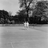 """Two men leaving a tennis court, 1955."""